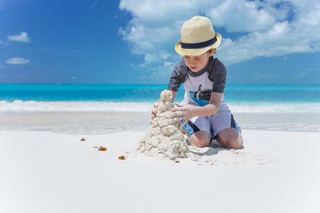Little boy making sand castle at the beach photo