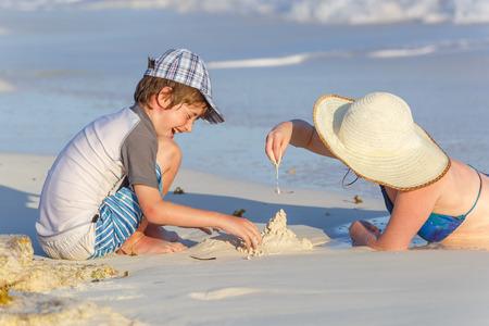 child bikini: Family making sand castle at the beach Stock Photo