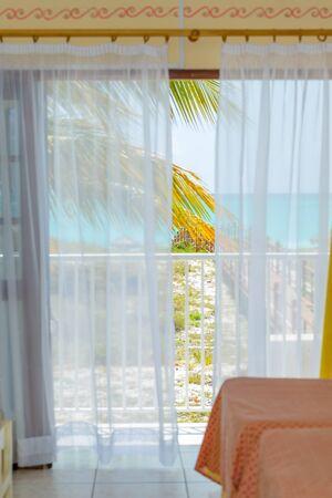 window view: Sea view through white curtains