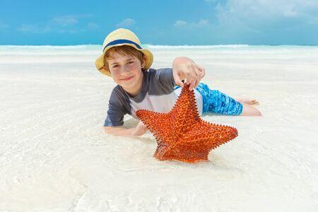 Boy and starfish on a tropical beach photo
