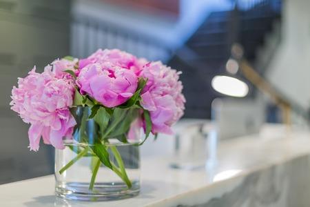 Interiores de una recepción médica oficina con hermosas flores de color rosa en el florero