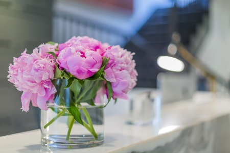 service desk: Interiors of a office medical reception with beautiful pink flowers in vase Stock Photo