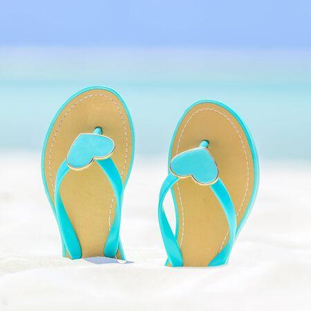 flops: Flip Flops with hearts on a sandy ocean beach Stock Photo