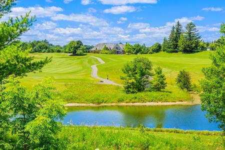 courses: Golf place with gorgeous green, pond and custom built luxury big house on background. Stock Photo