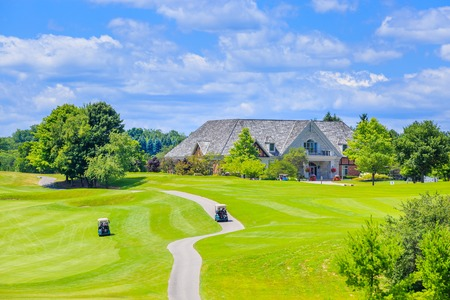 Golf place with gorgeous green and custom built luxury big house on background.