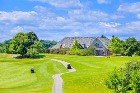 miejsce golf z pięknym zielonym i niestandardowy zbudowany luksusem dużego domu w tle.