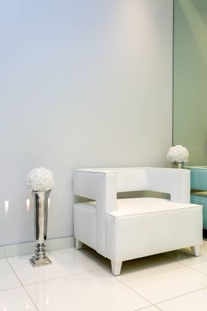 service entrance: Interior with white armchair and vase near white wall. Stock Photo