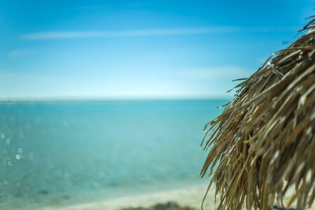 ocean background: Beach Umbrella made of palm leafs on the background of an exotic beach in Cayo Largo
