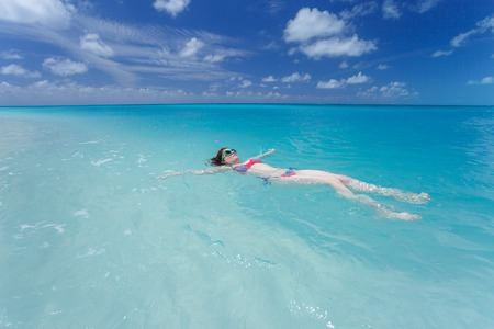pink bikini: Woman floating and relaxing in turquoise waters at colorful tropical beach