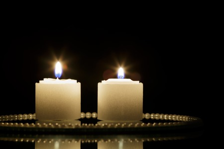 jesus birthday: Two Candles on mirror plate and black background Stock Photo