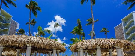 bungalows: Bungalows and blue sky with palms in Aruba resort Stock Photo