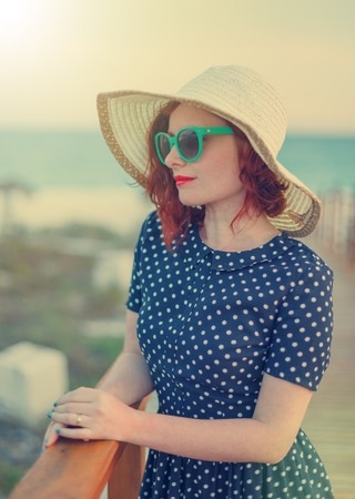 glamour girl: Red-haired girl in a hat and sunglasses on the background of the sea Stock Photo