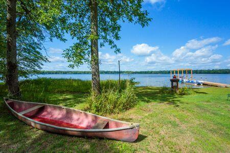 lake beach: Red canoe on a beach of lake. Canada