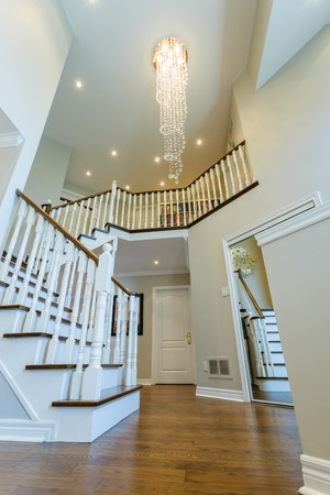 banister: Beautiful foyer looking down hardwood stairs in new house Stock Photo