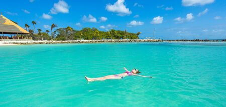 relaxing beach: Woman floating and relaxing in turquoise waters at colorful tropical beach