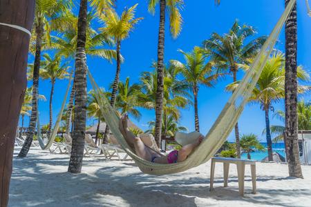 Woman in hat in a hammock on caribbean beach