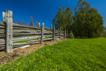 Wooden fence in green grass meadow Banco de Imagens