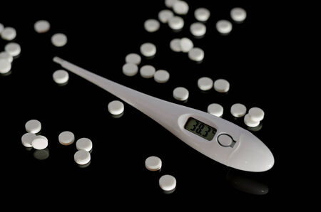 Thermometer and pills on a black background photo