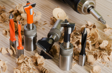 Machine tool cutters and drill bits in the sawdust on wood background