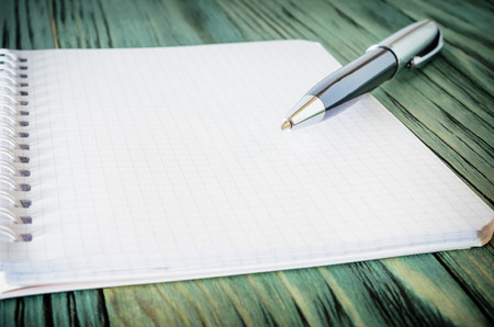 looseleaf: loose-leaf notebook with a pen on a table on a wooden background, close-up