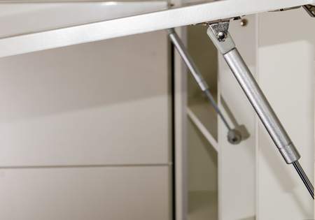 fronts: furniture rack, gas lift for the furniture fronts of kitchen units closeup Stock Photo