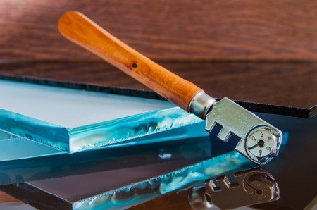 glass cutter: glass and glass cutter closeup on wooden background