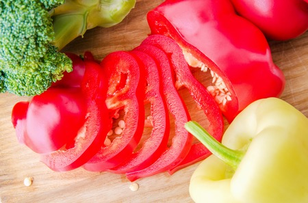 broccoli and tomato and red pepper on cutting board isolated on white Stock Photo