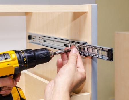 Het assembleren van meubels uit spaanplaat, met behulp van een accuschroevendraaier, close-up.