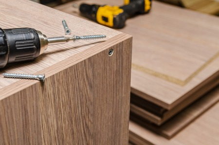 wenge: the process of furniture assembly screws closeup Stock Photo