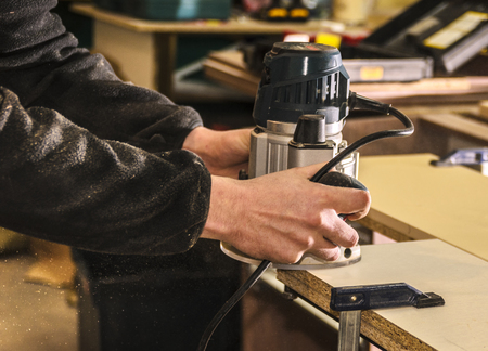 Employee workpieces for furniture hand router closeup