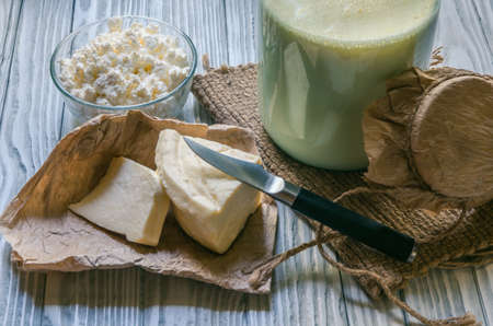 Homemade dairy products, milk, cottage cheese, etc. on a wooden background