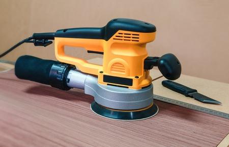 Electric orbital grinder on a background of dark oak veneer