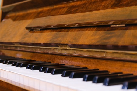 Open keys of an old piano closeup