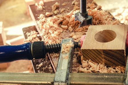 The master makes a hole in the wooden blank. Imagens