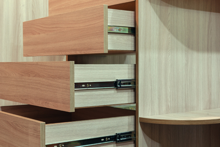 Wooden facades on the drawers close-up, cabinet furniture 免版税图像