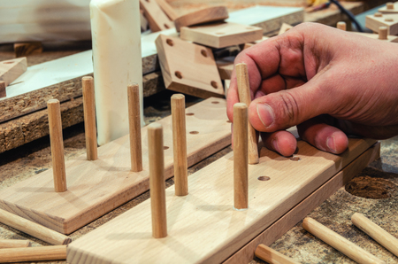 Carpentry workshop for the manufacture of wooden toys, the master glues the elements of childrens toys. Close-up 스톡 콘텐츠