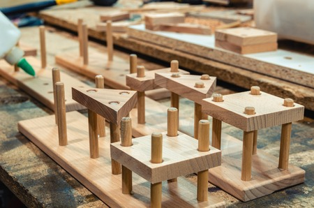 Carpentry workshop for the manufacture of wooden toys, the master glues the elements of children's toys. Close-up 스톡 콘텐츠 - 122267081