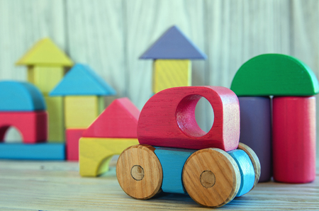 Wooden toys, typewriter and home from wooden constructor on wooden white background, close-up 스톡 콘텐츠
