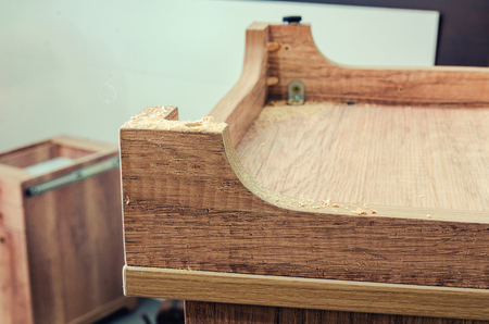 Carpentry workshop, work process, master glues and assembles an element of cabinet furniture