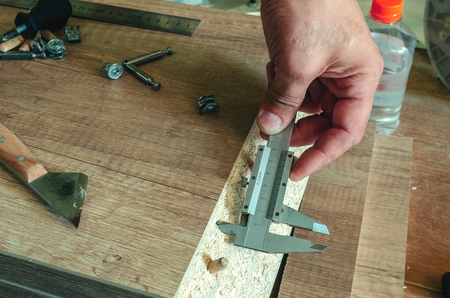 A carpenter measures the holes made with a caliper. Carpenter tools 스톡 콘텐츠
