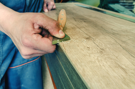 The master processes the edge of the furniture with a working knife