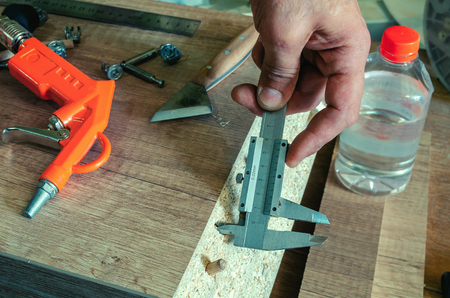 Carpenter measures the holes made with a caliper