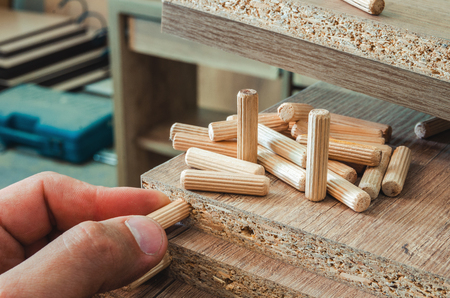 Furniture fittings, wooden dowels, fastener connection on chipboard workpieces, close-up 스톡 콘텐츠