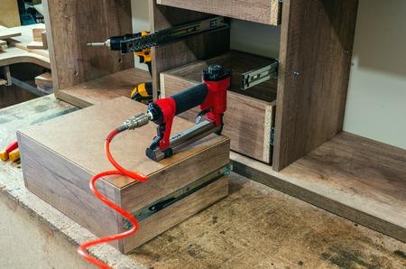 red pneumatic stapler in a furniture workshop