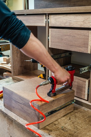 red pneumatic stapler in a furniture workshop, master nails a dong on the drawers 스톡 콘텐츠 - 125213298