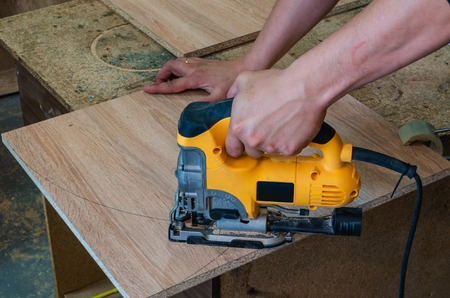The master cuts the workpiece from chipboard for the production of furniture electric jigsaw, close-up 스톡 콘텐츠 - 125213305