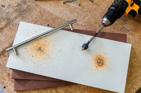 Assembling furniture, installing furniture decorative handles on the furniture facade