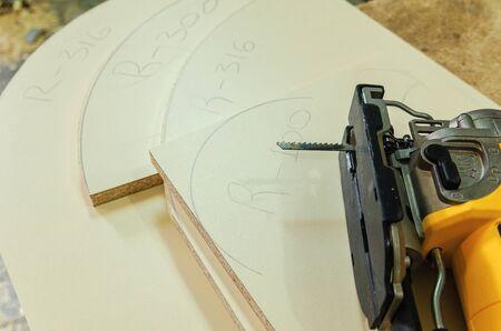 Elektrische Stichsäge schneidet das Werkstück aus Spanplatten für Möbel