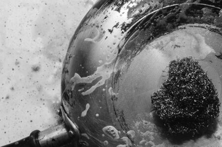 Cleaning ngara in a pan with a metal scraper with detergent, black and white photo, close-up