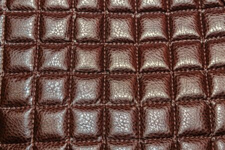 Background from brown leather upholstered furniture, stitched rhombus.